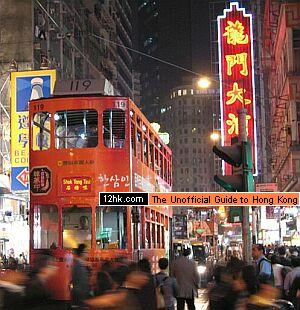 above wan chai area at night with a tram stopping at a traffic light